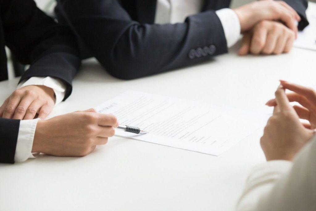 תמונה של כמה אנשים שקוראים חוזה או הסכם לפני חתימה