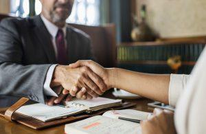 תמונה של שני אנשים לוחצים ידיים בהקשר של הסכמים וחוזים