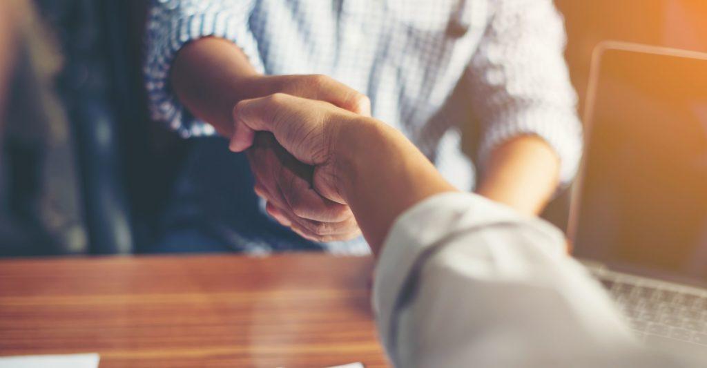תמונה של לחיצת יד בין שתי שותפים עסקיים המתארת את חשיבותו של עורך דין הסכם מייסדים